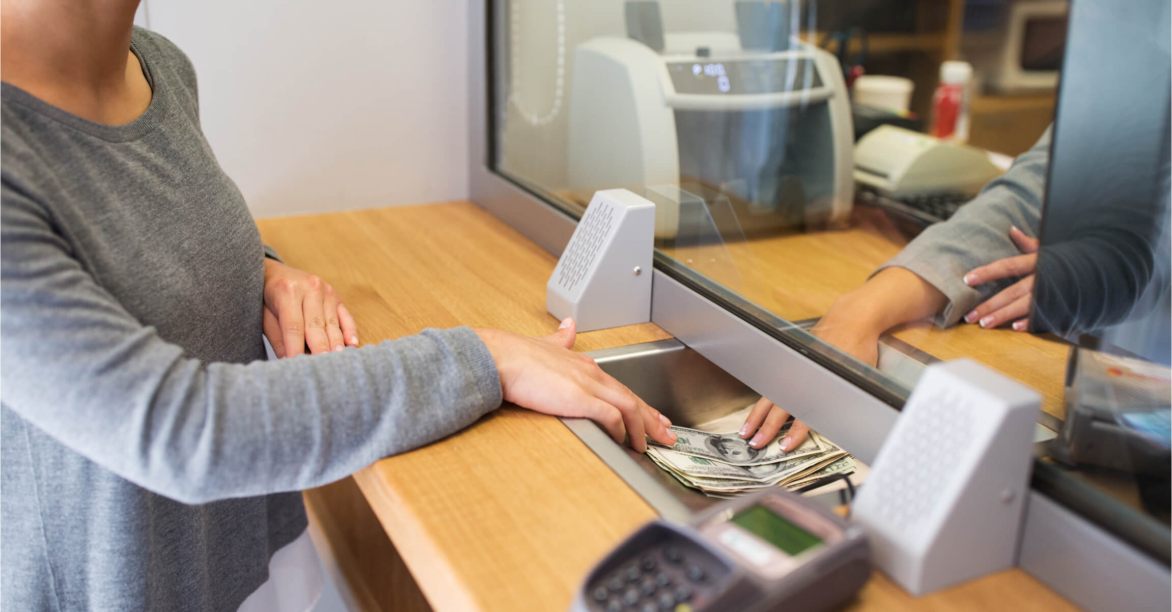 customer depositing funds to bank teller.