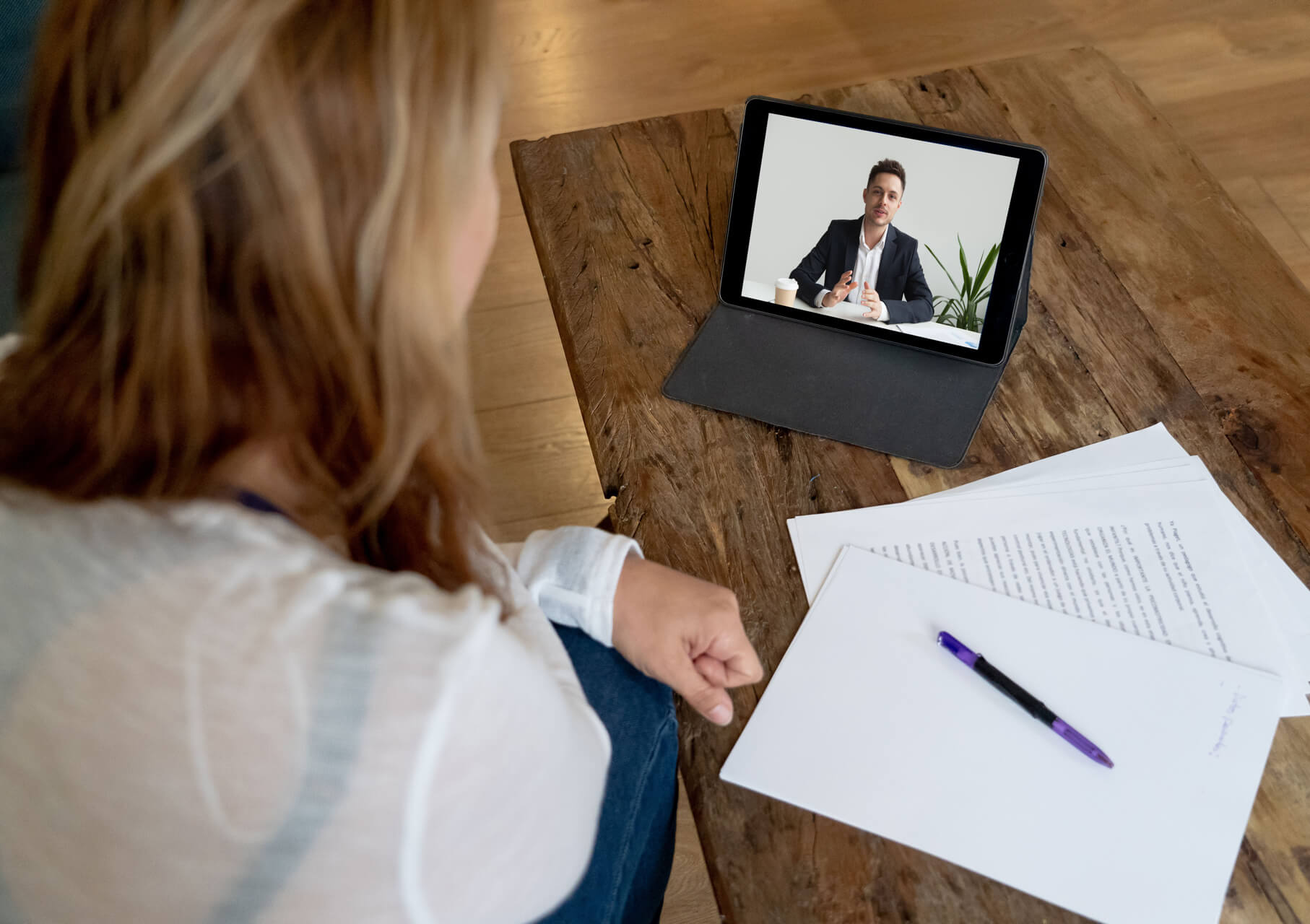 Professional on tablet video call with documents.