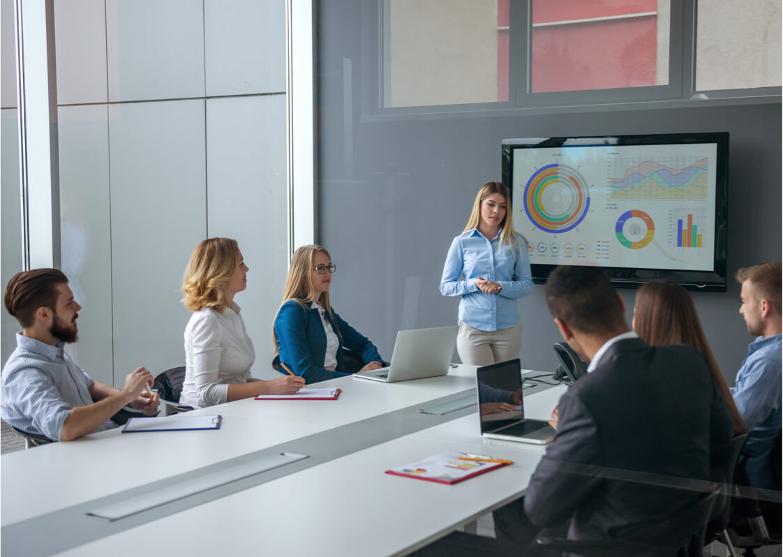 Professional presenting colorful data slides in meeting room.