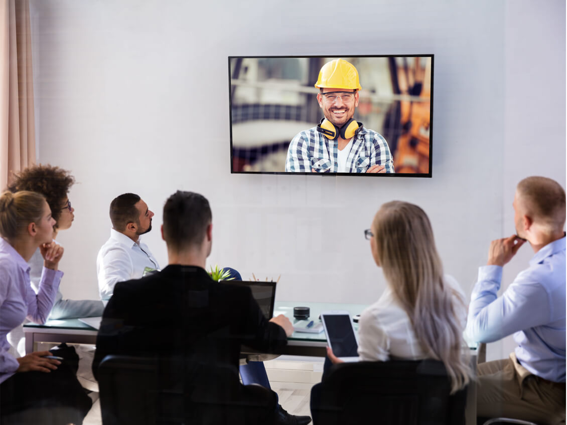 Professionals in meeting with happy construction worker.