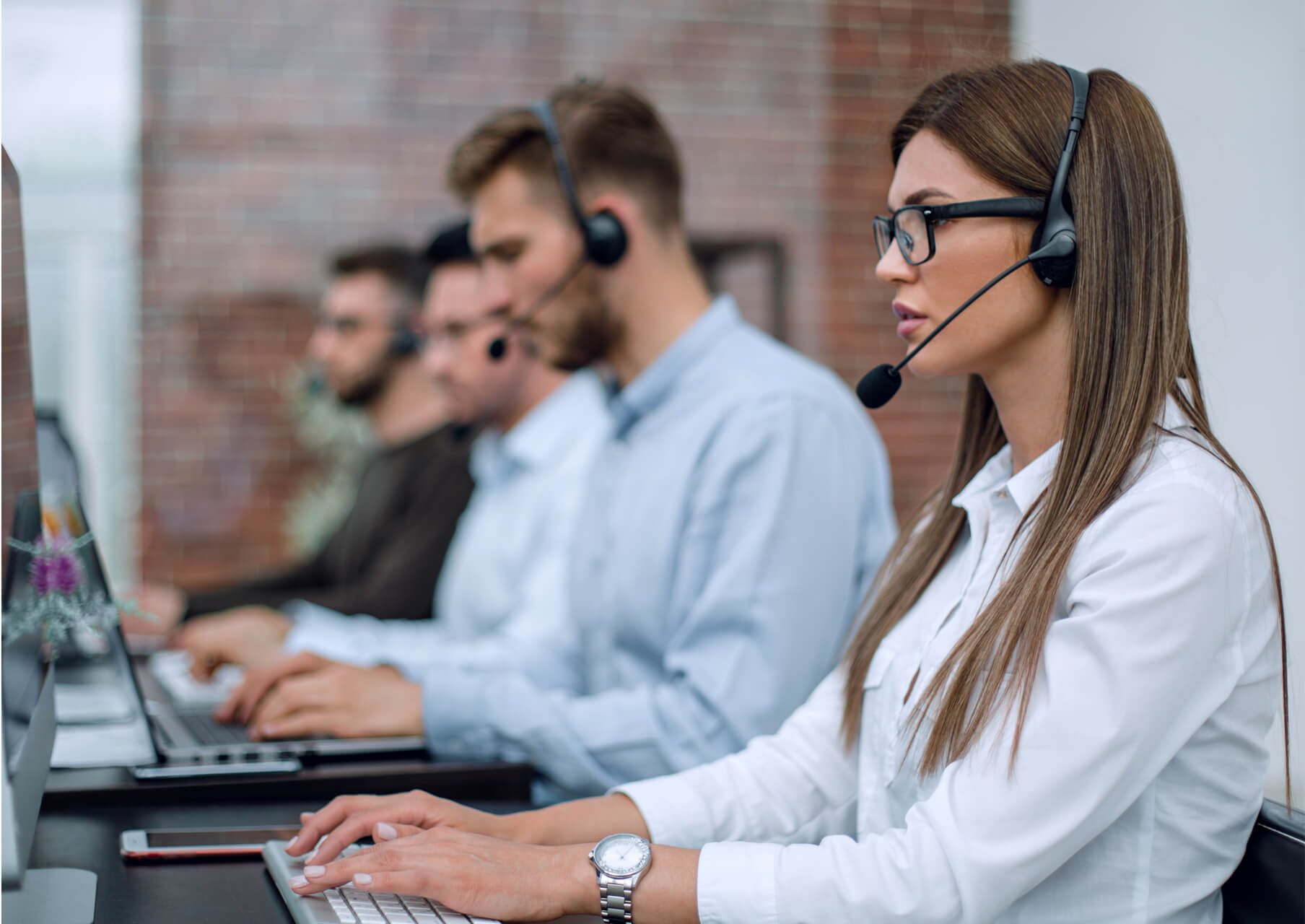 Professionals sitting in a row on headsets and desktops.