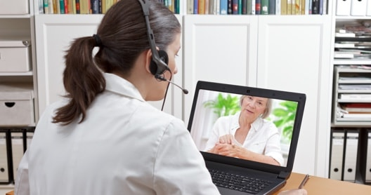 Health care individual communicating with patient via video.
