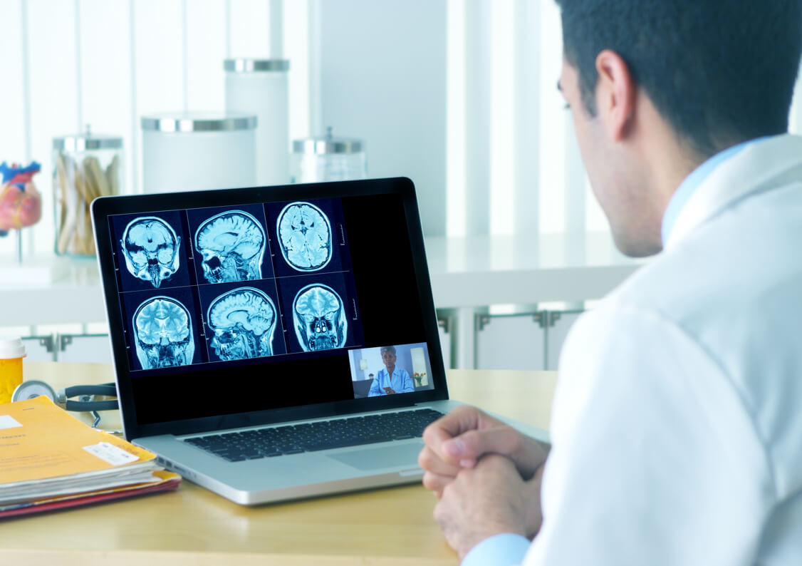 Health professional viewing mri on laptop screen.