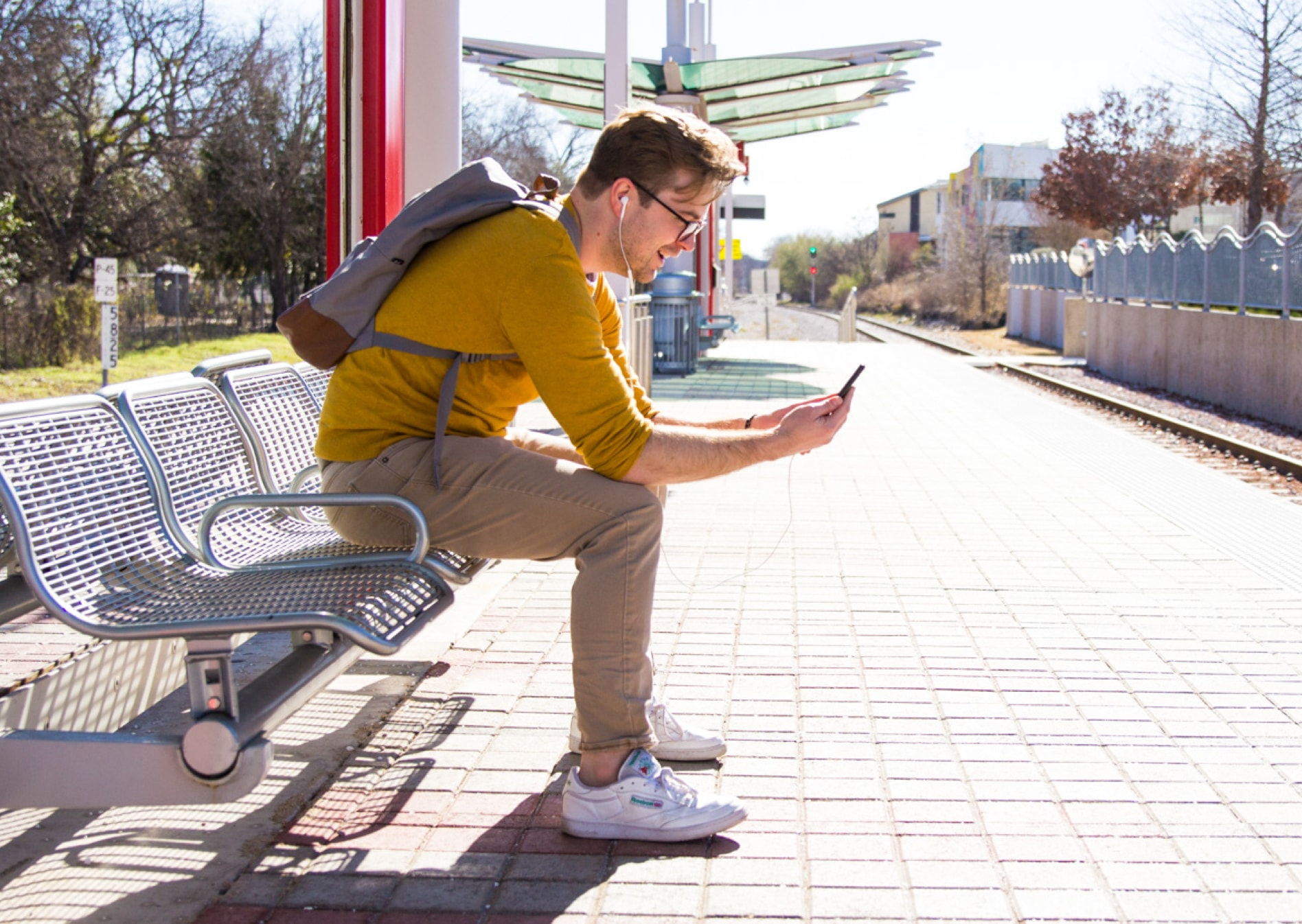 A man sitting on a bench in the city, in a video conference, using a cellphone.