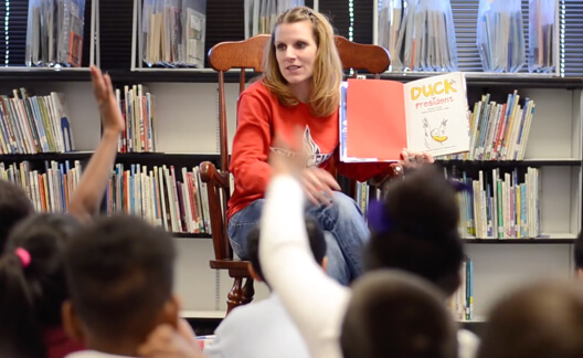 Teacher reading picture book to young students.