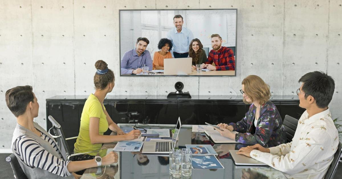 4 People sitting in a conference room on a video call with 5 people