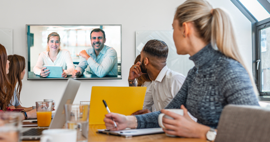 Group video conference in a modern office space.