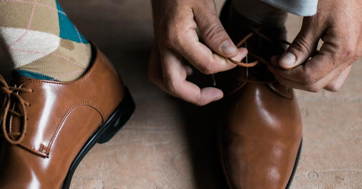 A man tying his dress shoes, preparing to go to work